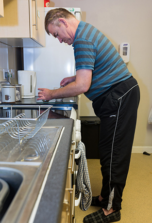 Image of service user washing up