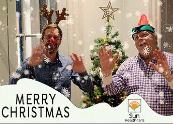Men in Christmas hats waving